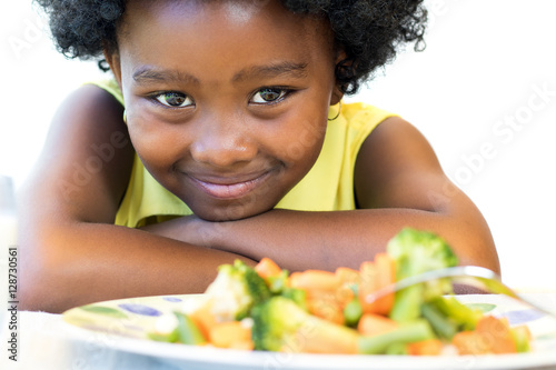 Fotografiet African girl in front of vegetable dish.