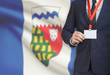 Businessman holding badge on a lanyard with Canadian province flag on background - Northwest Territories
