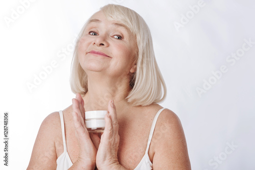 Poster Nice happy woman using anti age cosmetics