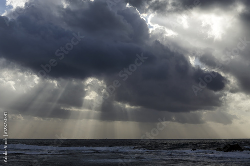 Stormy sea sky with sunbeams