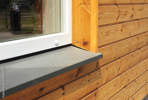 Window Sill with Modern Wooden Facade Wall. Single plastic window sill detail. Install window.