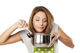 attractive young woman enjoying the smell of food from the pot