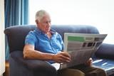Senior man seated on a sofa reading