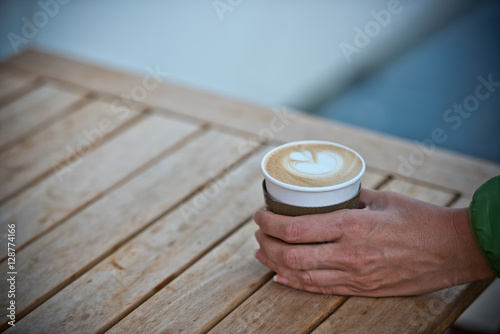 Poster Female hand holding a paper coffee cup