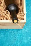Wine bottle lying on straw in vintage wooden box.