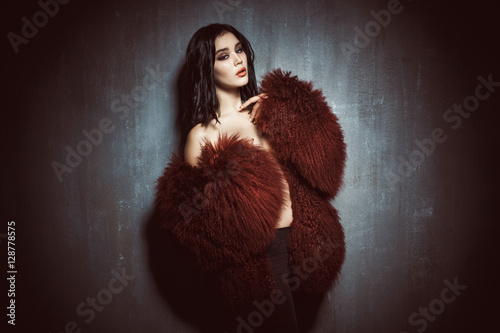 Plakát, Obraz young beautiful girl in the big red and fluffy coat is standing