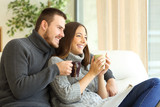 Happy couple thinking and holding hot drinks in winter
