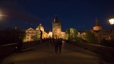PRAGUE, CZECH REPUBLIC - APRIL 28, 2016: Hyperlapse shot of moving along Charles Bridge at night. People walking from and to Old Town Tower. Gothic style bridge gate
