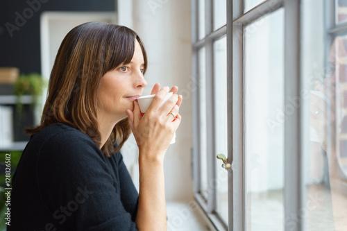 Poster art print frau steht am fenster und trinkt einen for Fenster 60x40