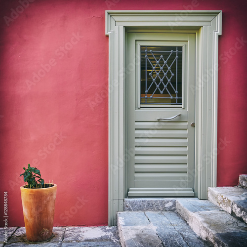 Poster grey door on colorful fuchsia house wall and a flowerpot, filtered