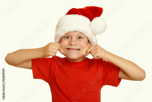 Fotografiet boy child make faces in santa hat, having fun and emotions, winter holiday conce