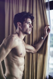 Sexy handsome young man standing shirtless in his bedroom next to window curtains