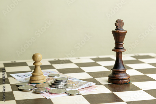 Zdjęcia The chess king, pawn and money on a chessboard