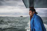 Profile shot of a man on a boat looking at an ocean over the railing