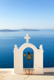 Church bell in Oia, Santorini, Greece. Sea and volcano on backgr
