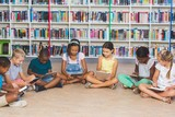 Fototapety School kids sitting on floor using digital tablet in library