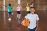 Boy standing with ball in basketball court