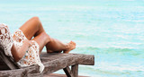 Woman is lying in the in wooden chaise lounge at the beach