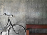 One Bike,Bicycle vintage style on Concrete wall and wood chair.