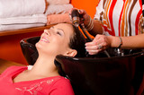 Hairdresser washing hair of beautiful girl in hairdressing salon