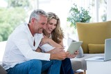 Smart mature couple using digital tablet - 128885134