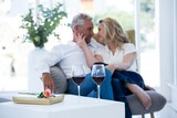Romantic couple sitting on armchair with wine and gift box
