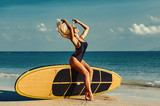 Sexy young woman with hair flowing posing with a surfboard on th