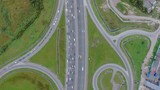 Top view of a highway with a lot of cars, green grass and the industrial zone