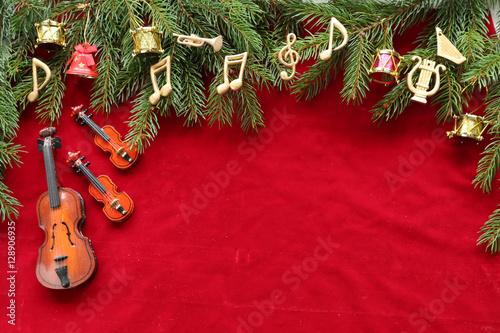 Fototapeta Musical notes, instruments on christmas tree brunch on red velvet
