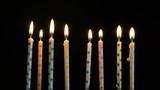 Footage colorful burning candles set on black background. 4k