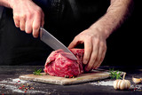 Fototapety Man cutting raw beef meat