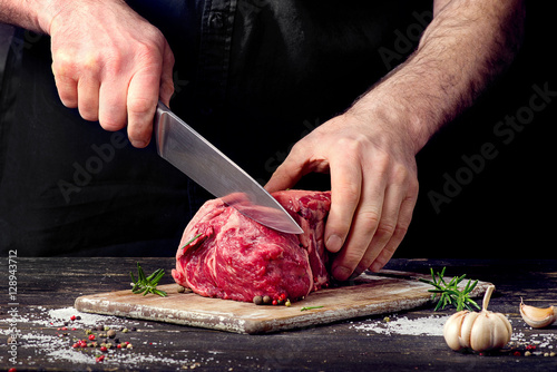 Poster Man cutting raw beef meat