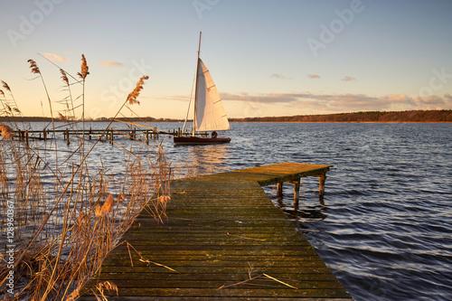 Segelboot im Sonnenlicht am Steg Poster