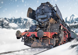 Classic locomotive train on snowy railway amidst the mountains