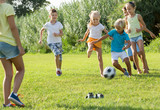 Group of active kids playing football together on green lawn in