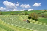 Zwei Traktoren bei der Ernte von Grünfutter in hügeliger Landschaft