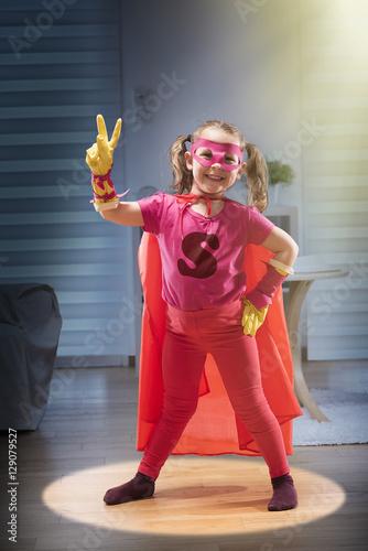 Little girl dressed as super hero in her living room Poster