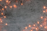 Christmas lights frame on dark grey stone background