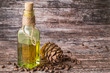 Постер, плакат: Cedar oil Cedar oil in a glass bottle and a cedar cones with nuts on a brown wooden background