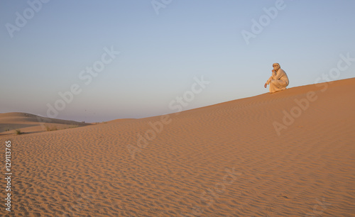 Papiers peints Abou Dabi man in traditional outfit in a desert near Dubai