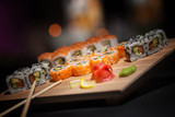 Appetizing rolls lie on a wooden plate. Traditional serving. Wasabi, lemon. The atmosphere is warm, cozy restaurant. Creative color.
