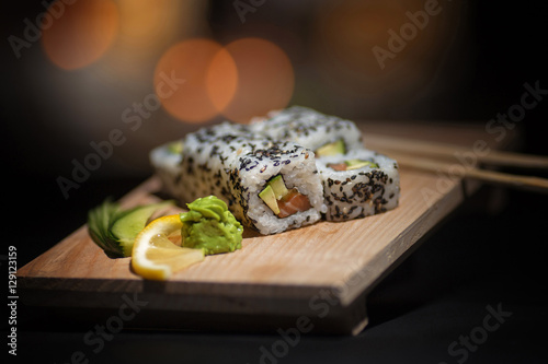 Fotobehang Sushi bar Appetizing rolls lie on a wooden plate. Traditional serving. Wasabi, lemon. The atmosphere is warm, cozy restaurant. Creative color.