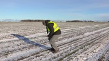Farmer using tablet on field of snow covered plants