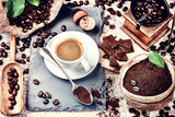 Fototapety Cup of hot black coffee in setting with roasted coffee beans
