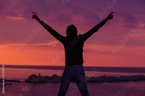 Keuken foto achterwand Crimson Young adult raising arms to the sea at sunset hands up