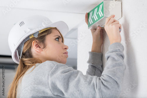Poster Woman fixing exit sign to wall
