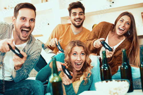 Poster Excited friends playing video games at home