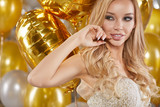 portrait of blond young woman between golden balloons. New Year