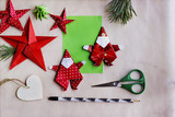 Figuras para decoración navideña hechas de papel con técnica origami, tijeras y lapicero sobre fondo de papel texturizado. Imagen capturada utilizando la suave luz de una ventana. Plano cenital - 129214166