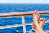 Relaxation on cruise ship travel holiday. Closeup of women feet up on balcony overlooking ocean view on caribbean vacation at sea. Barefoot woman sun tanning relaxing at outdoor spa.